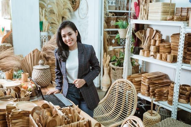 Attraktive asiatische geschäftsinhaberin in ihrem kunst- und handwerksgeschäft, die waren aus naturprodukten verkauft