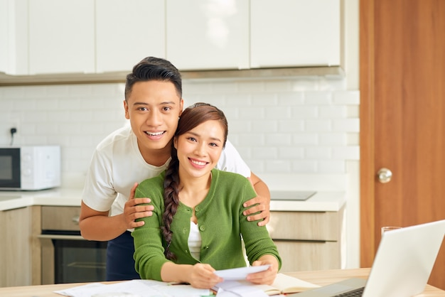 Attraktive asiatische hausfrau, die glücklichen ausdruck beim berechnen von rechnungen in der küche hat