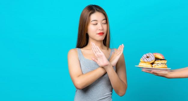 Attraktive asiatische junge frau, die keine aktion mit schaumgummiringen auf lokalisierter blauer wand, gewichtsverlust tut und ungesunde fertigkost für gesundes konzept, kopienraum und studio vermeidet