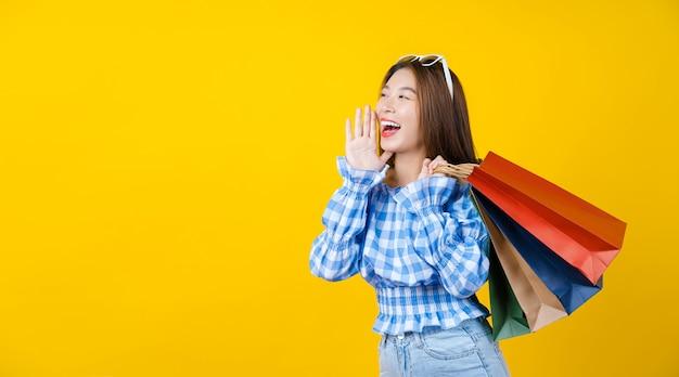 Attraktive asiatische lächelnde junge frau, die coloful einkaufstasche auf aisolated gelber wand trägt