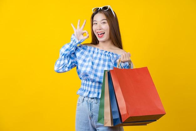 Attraktive asiatische lächelnde junge frau, die eine coloful einkaufstasche trägt und okayzeichen zur vereinbarung über aisolated gelbe wand gestikuliert