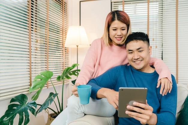 Attraktive asiatische süße paare unter verwendung der tablette beim lügen auf dem sofa, wenn in ihrem wohnzimmer sich entspannen