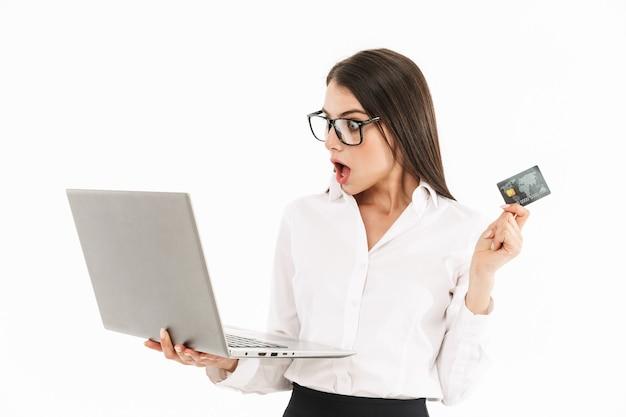 Attraktive aufgeregte junge geschäftsfrau, die isoliert über weißer wand steht, laptop-computer hält und kreditkarte zeigt