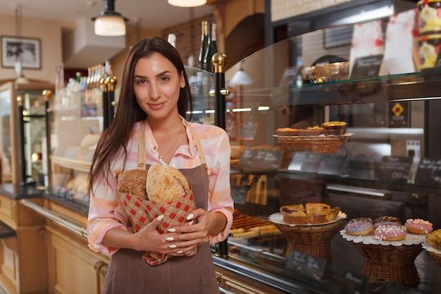 Attraktive bäckerin in einer konditorei