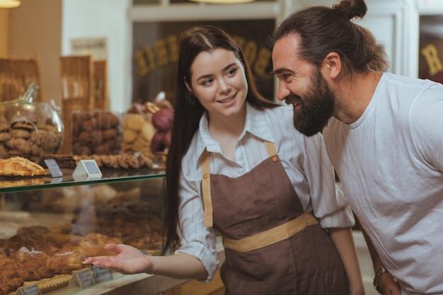 Attraktive bäckerin mit schürze, die ihren kunden gebäck auf dem display anbietet