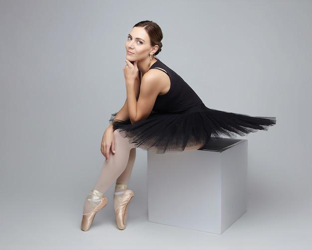 Attraktive ballerina posiert anmutig beim sitzen auf einem würfel auf weißem hintergrund