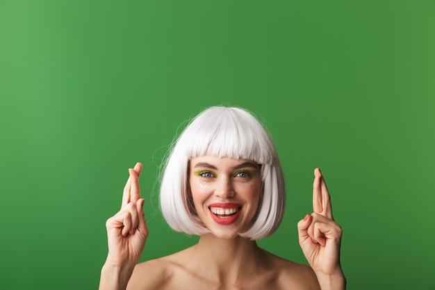 Attraktive besorgte junge topless frau, die kurzes weißes haar trägt, das isoliert steht und daumen drückt für glück