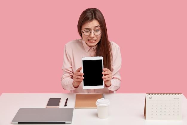 Attraktive bloggerin beißt die zähne zusammen, hält brocken-tablette, kann nicht verstehen, warum es nicht funktioniert, hat viele dinge ordentlich auf dem schreibtisch angeordnet, trinkt kaffee