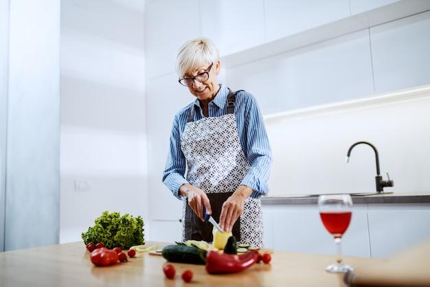 Attraktive blonde ältere frau in der schürze, die in der küche zu hause steht und gelben pfeffer schneidet