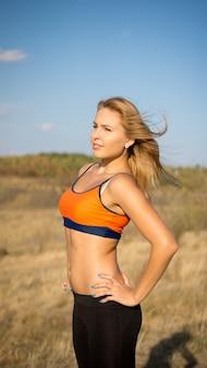 Attraktive blonde athletische frau in einem sport-bh mit einem nackten zwerchfell, der seitlich mit dem wind in ihren haaren in offener landschaft aufwirft