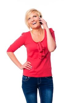 Attraktive blonde frau, die auf ihrem handy spricht
