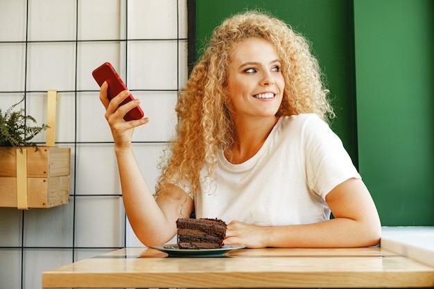 Attraktive blonde frau, die im café sitzt und ihr handy benutzt