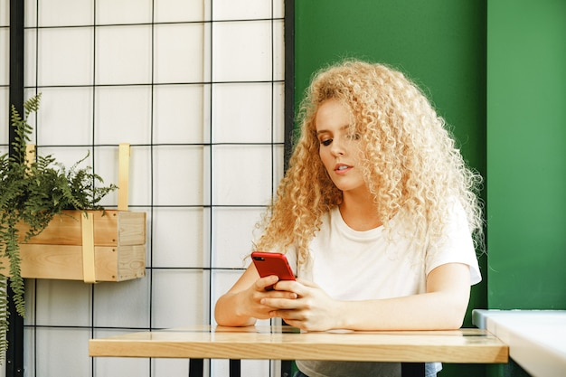 Attraktive blonde frau, die nahe fenster im café sitzt und ihr handy benutzt