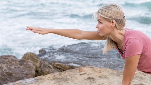 Attraktive blonde frau, die yoga im freien tut