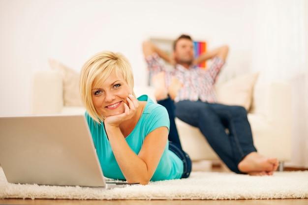 Attraktive blonde frau mit computer auf dem teppich