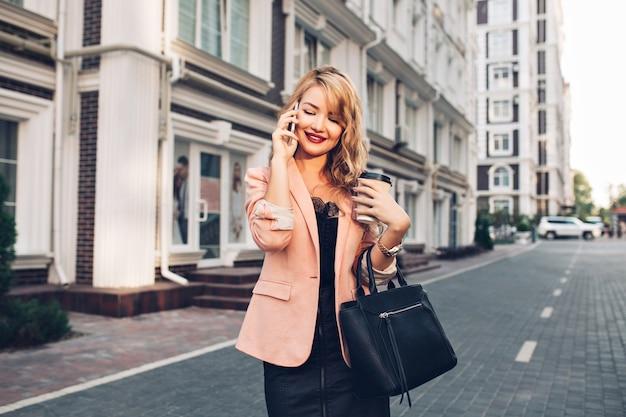 Attraktive blonde frau mit langen haaren, die in der korallenjacke auf straße gehen. sie telefoniert, hält eine tasse in der hand und lächelt nach unten.