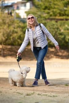 Attraktive blonde frau mittleren alters, die mit hund in der sommerstadt geht.