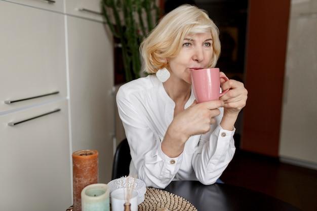 Attraktive blonde frau mittleren alters, die sich zu hause in der küche entspannt und kaffee trinkt