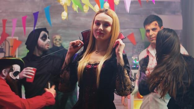 Attraktive blonde frau verkleidet wie sexy hexe für halloween-party mit ihren freunden verkleidet wie verschiedene monster.