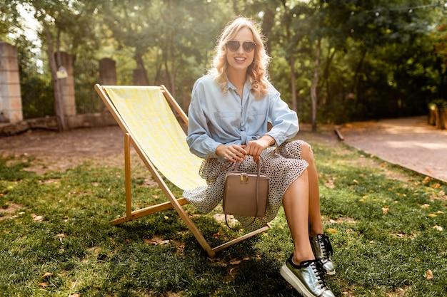 Attraktive blonde glückliche frau, die entspannend im liegestuhl im blauen hemd des sommeroutfits sitzt und silberne turnschuhe, elegante sonnenbrille und geldbörse trägt