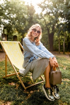 Attraktive blonde glückliche frau, die entspannend im liegestuhl im sommeroutfit sitzt
