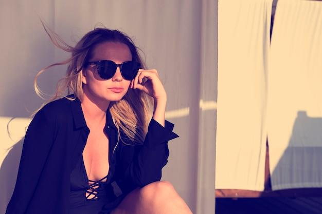 Attraktive blonde junge frau mit sonnenbrille im strandbungalow auf dem sonnenuntergang