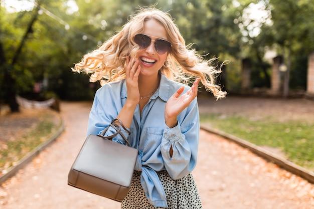 Attraktive blonde lachende offene frau, die im park im blauen hemd des stilvollen outfits geht, das elegante sonnenbrille und geldbörse trägt