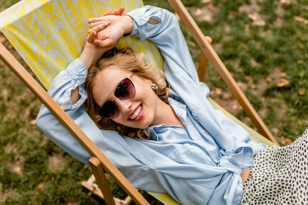 Attraktive blonde lächelnde frau, die entspannt im liegestuhl im stilvollen outfit sitzt