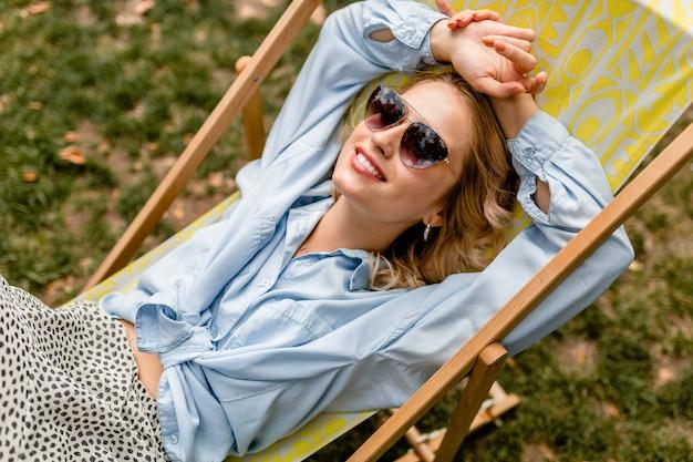 Attraktive blonde lächelnde frau, die im liegestuhl im sommeroutfit sitzt