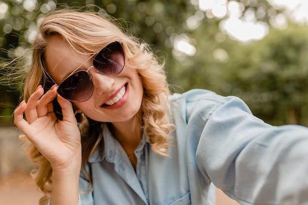 Attraktive blonde lächelnde frau, die im park im sommeroutfit geht und selfie-foto am telefon macht