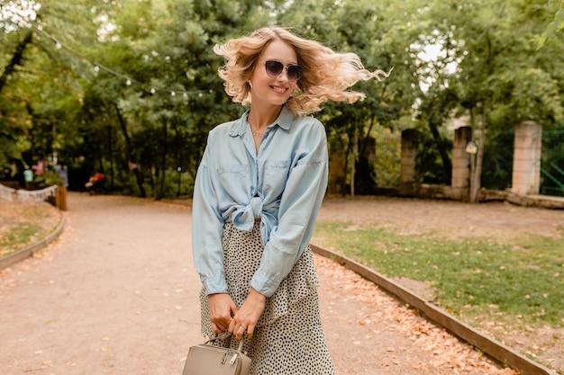 Attraktive blonde lächelnde offene frau, die im park im sommeroutfit geht