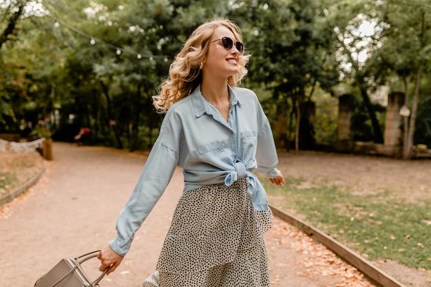 Attraktive blonde lächelnde offene frau, die langes haar winkt, das spaß hat, im park im sommeroutfit zu gehen