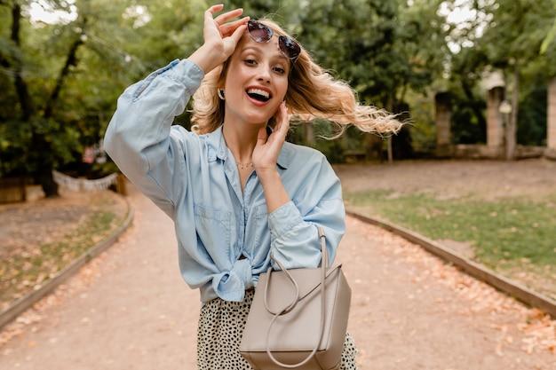 Attraktive blonde offene frau, die im park im stilvollen outfit geht, das elegante sonnenbrille und geldbörse trägt