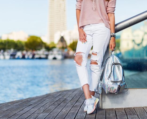 Attraktive blonde touristenfrau, die draußen im sonnigen tag, windiges wetter aufwirft. helles make-up. trägt einen rosa pastellpullover und einen neonrucksack. einzelheiten.