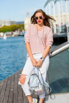 Attraktive blonde touristenfrau, die draußen im sonnigen tag, windiges wetter aufwirft. helles make-up. trägt einen rosa pastellpullover und einen neonrucksack.