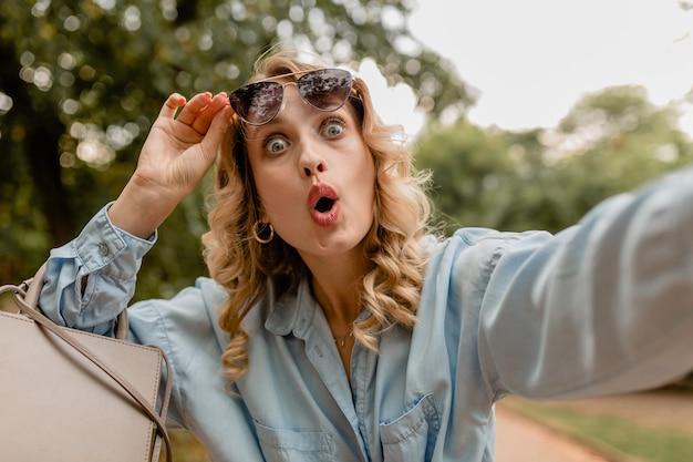 Attraktive blonde überraschte lustige frau im sommeroutfit, das selfie-foto am telefon macht