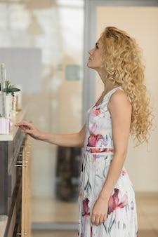 Attraktive blondine im café, hält ein menü und wählt kaffee.
