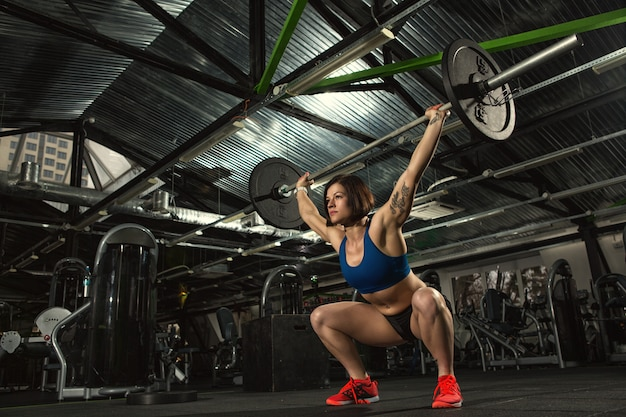 Attraktive bodybuilderin, die schwere kniebeugen macht, die langhantel im fitnessstudio heben