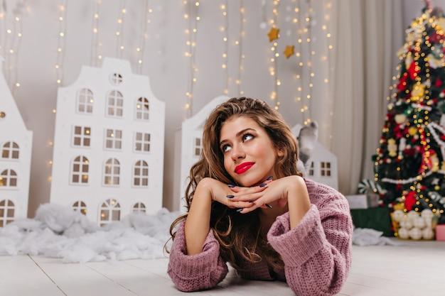 Attraktive braunhaarige frau mit roten lippen und süßem lächeln liegt in einem dekorierten weißen raum, gefüllt mit weihnachtsspielzeug und üppigem weihnachtsbaum.