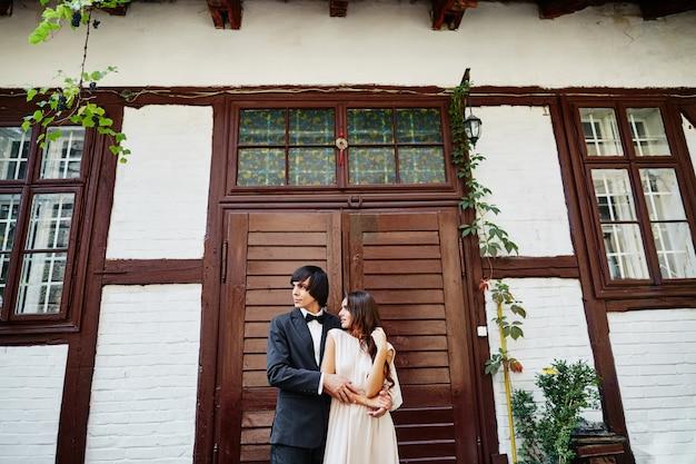 Attraktive braut und bräutigam, die nahe beieinander am alten haushintergrund, hochzeitsfoto, schönes paar, hochzeitstag, porträt stehen.