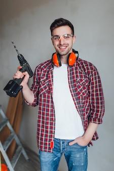 Attraktive brillen des erbauers n und mit einem bohrgerät in seinen händen