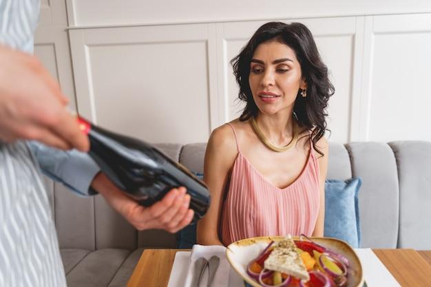 Attraktive brünette dame, die am tisch mit leckerem essen sitzt, während die café-arbeiterin eine flasche alkoholisches getränk hält