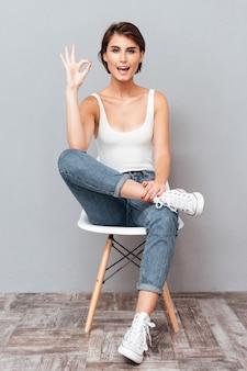 Attraktive brünette frau, die auf dem stuhl sitzt und okay zeichen über grauem hintergrund zeigt