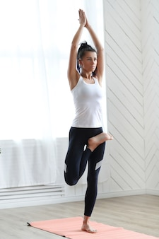 Attraktive brünette frau, die yoga zu hause macht.