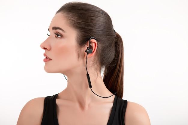 Attraktive brünette frau im rüttelnden schwarzen oberteil, das musik auf kopfhörern hört, die lokal auf weißem hintergrund pferdeschwanzfrisur posieren