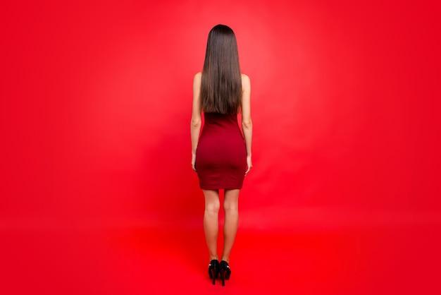 Attraktive brünette frau in einem roten kleid, das gegen die rote wand aufwirft