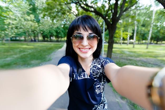 Attraktive brünette frau macht selfie-fotos, die zur kamera schauen