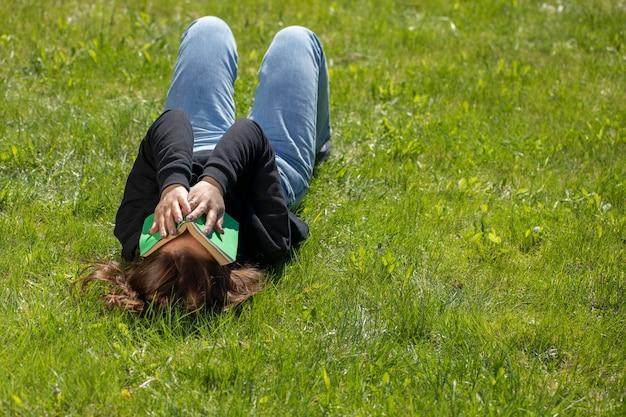 Attraktive brünette frau mit langen haaren gekleidet im schwarzen kapuzenpulli, der auf gras des grünen rasens an schönem sommertag liegt, der ihr gesicht mit buch bedeckt