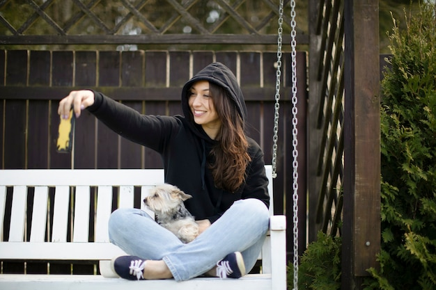 Attraktive brünette frau mit langen haaren gekleidet im schwarzen kapuzenpulli, der auf weißer schaukelbank mit yorkshire-hund sitzt und selfies mit ihrem smartphone macht