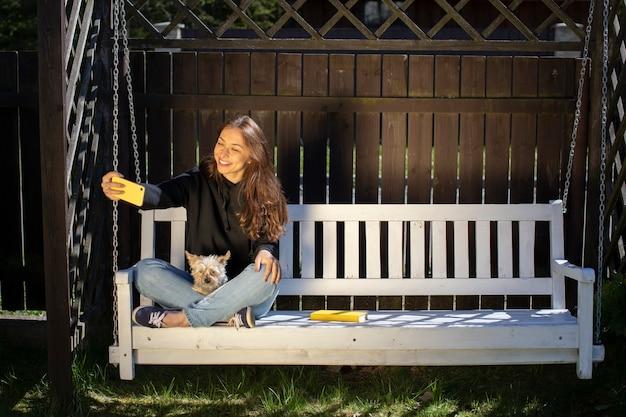 Attraktive brünette frau mit langen haaren im schwarzen kapuzenpulli macht selfies auf weißer schaukelbank mit yorkshire-hund